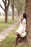Young girl leaning against a tree. And staring at far away Stock Image