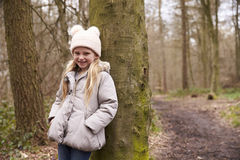 Young girl leaning against a tree by a path in a forest Stock Photo