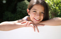 Young girl leaning on blank board Royalty Free Stock Image