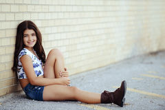 Young girl leaning on brick wall Royalty Free Stock Photos