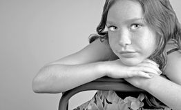 Young girl leaning on chair stock photo