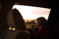 Young girl leaning out a car window. Royalty Free Stock Photos