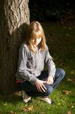 Young girl leaning on a tree Stock Photo