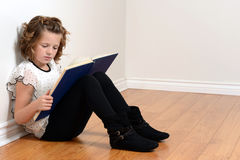 Young girl leaning on wall reading book Stock Images