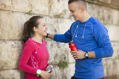 Young girl leaning on wall talking to young man Royalty Free Stock Images