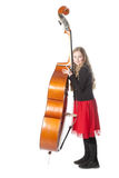 Young girl leans against double bass in studio Stock Photos