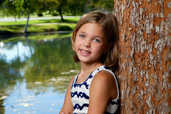 Young Girl Leans Against Tree. A beautiful, young girl leans against a tree in a park in front of a pond Stock Photo