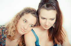 A young girl leans on girl friend's shoulder Royalty Free Stock Photos