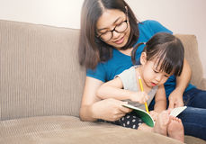 Young girl learning how to write with her mother Royalty Free Stock Photo