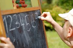 Young girl learning numbers. Very young girl learning how to write numbers on a blackboard Royalty Free Stock Photos