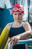 Young girl learning to swim in the pool with foam board Stock Image