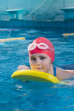 Young girl learning to swim in the pool with foam board. Young girl learning to swim in the pool Stock Image