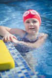 Young girl learning to swim in the pool with foam board stock photos