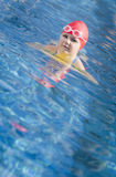 Young girl learning to swim in the pool with foam board royalty free stock photography