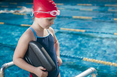 Young girl learning to swim in the pool with foam board Stock Photo