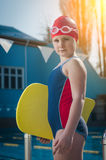 Young girl learning to swim in the pool with a foam board Stock Photography