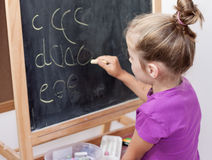 Young girl learning to write letters on blackboard. Young blond five years old caucasian girl learning to write letters on blackboard Royalty Free Stock Images