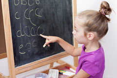 Young girl learning to write letters on blackboard. Young blond five years old caucasian girl learning to write letters on blackboard Royalty Free Stock Photos