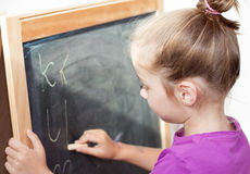 Young girl learning to write letters on blackboard. Young blond five years old caucasian girl learning to write letters on blackboard Stock Photo
