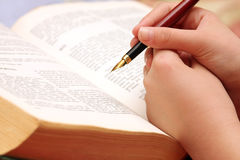 A young girl learns from an old book with pen in hand Royalty Free Stock Images