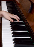 The young girl learns to play a piano Stock Image