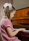 The young girl learns to play a piano Royalty Free Stock Image