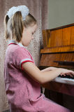 The young girl learns to play a piano Royalty Free Stock Photos