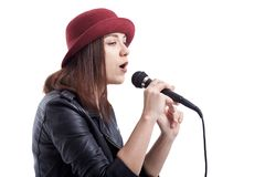 Young girl in leather hip jacket and red hat singing with microp Stock Photography