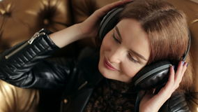 A young girl in a leather jacket listening to music in stereo headphones. stock footage