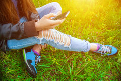 Young girl in leather jacket and ripped jeans sitting on the grass in the park and talking to friends on the phone Stock Photography