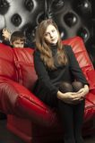 Young girl on a leather sofa Stock Image