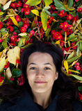Young girl among leaves and flowers. Young dark-haired girl  is lying among fallen yellow leaves and red flowers, looking straight to the camera Stock Photo