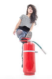 Young girl with leg on fire extinguisher Royalty Free Stock Photo