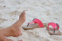 Young girl legs and flip-flop on the sand beach Royalty Free Stock Photo