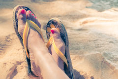 Young girl legs and flip-flop on the sand beach Royalty Free Stock Image