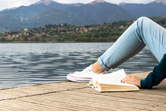 Young girl legs lies on a pier and reading a book Royalty Free Stock Images