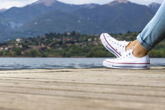 Young girl legs on a pier with blue jeans and white shoes Royalty Free Stock Photo
