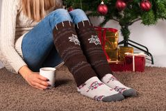 Young girl legs with warmers socks sitting on carpet floor and holding cup of coffee, Christmas tree and presents box in backgroun. Young female legs with Stock Photo