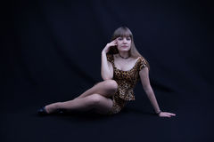Young girl in a leopard dress. Young girl in a leopard print dress on black background royalty free stock photo