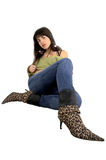 Young girl with leopard boots. Young girl seating by the wall Stock Images