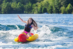Young girl lets go of inflatable while tubing Royalty Free Stock Image