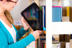 Young Girl in library with e-book or tablet computer. Student - young woman or girl taking a tablet computer with e-book out off the bookshelf stock images