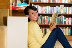 Young Girl in library reading book Royalty Free Stock Photos