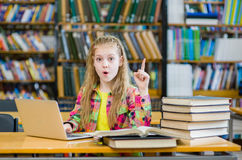 Young girl in the library showing finger up Royalty Free Stock Images