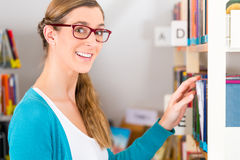Young Girl in library. Student - young woman or girl taking a book or textbook out off the bookshelf royalty free stock photo