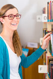 Young Girl in library. Student - young woman or girl taking a book or textbook out off the bookshelf royalty free stock images
