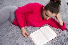 Young girl lies on bed and reads book at home. Attractive brunette woman with opened book. Stock Photography