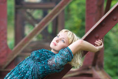 Young  girl lies on bridge bearing Royalty Free Stock Images