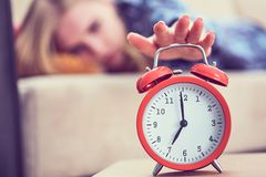Young girl lies on the couch and stretches her hand to the red alarm clock to turn it off. Late wake up. royalty free stock photos