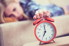Young girl lies on the couch and stretches her hand to the red alarm clock to turn it off. Late wake up. stock photos